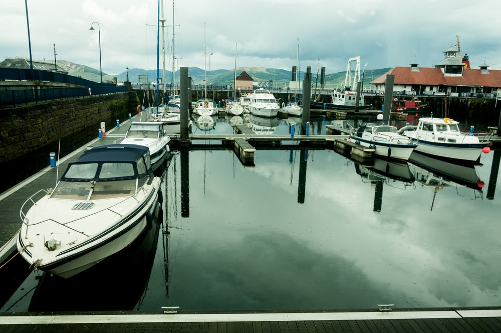 white speedboats dock on harbour during daytime