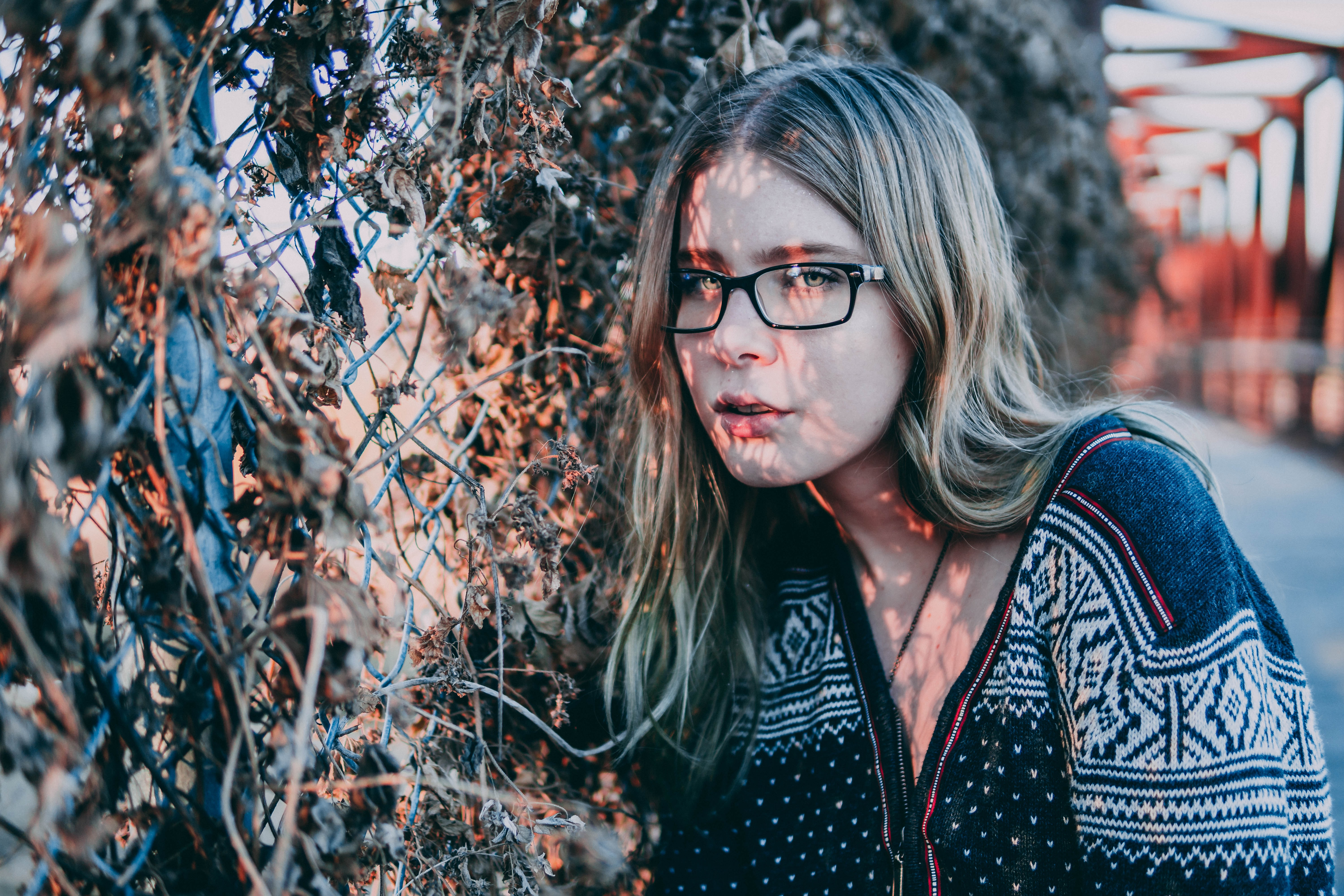 lights reflecting on woman's face standing beside green plant