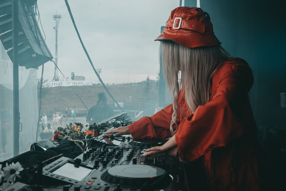 female DJ in red blouse using black DJ software controller during daytime