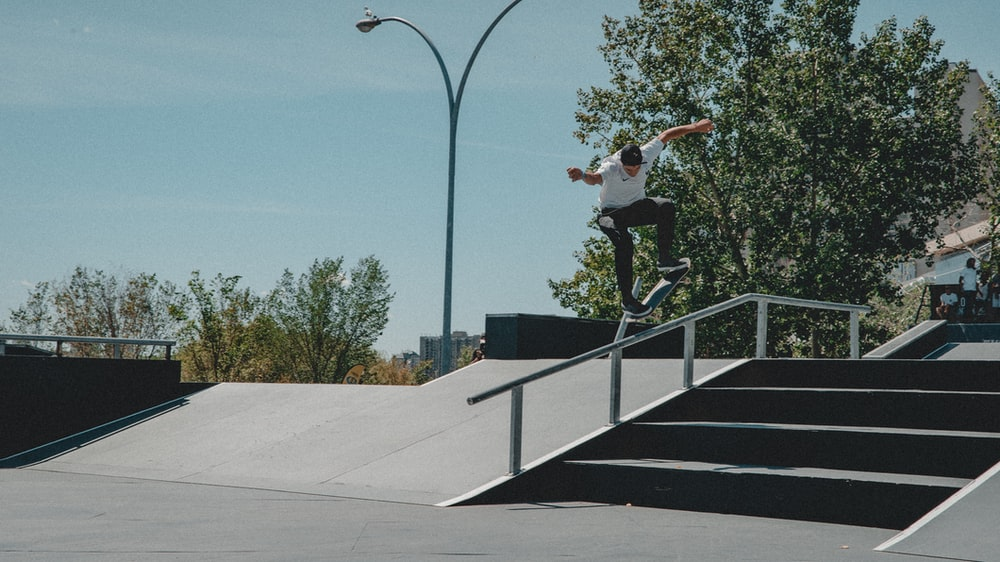 man in white shirt performing skateboard stunts on rail during daytime