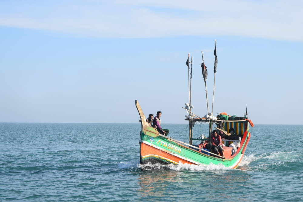 three people riding on green and red boat during daytime