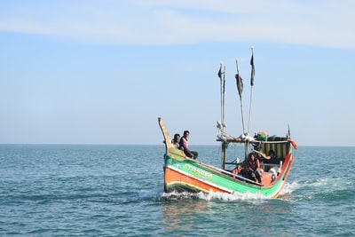 three people riding on green and red boat during daytime bangladesh zoom background