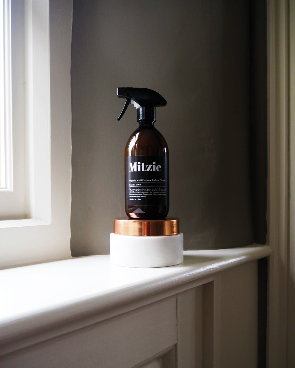 black Mitzie spray bottle near window