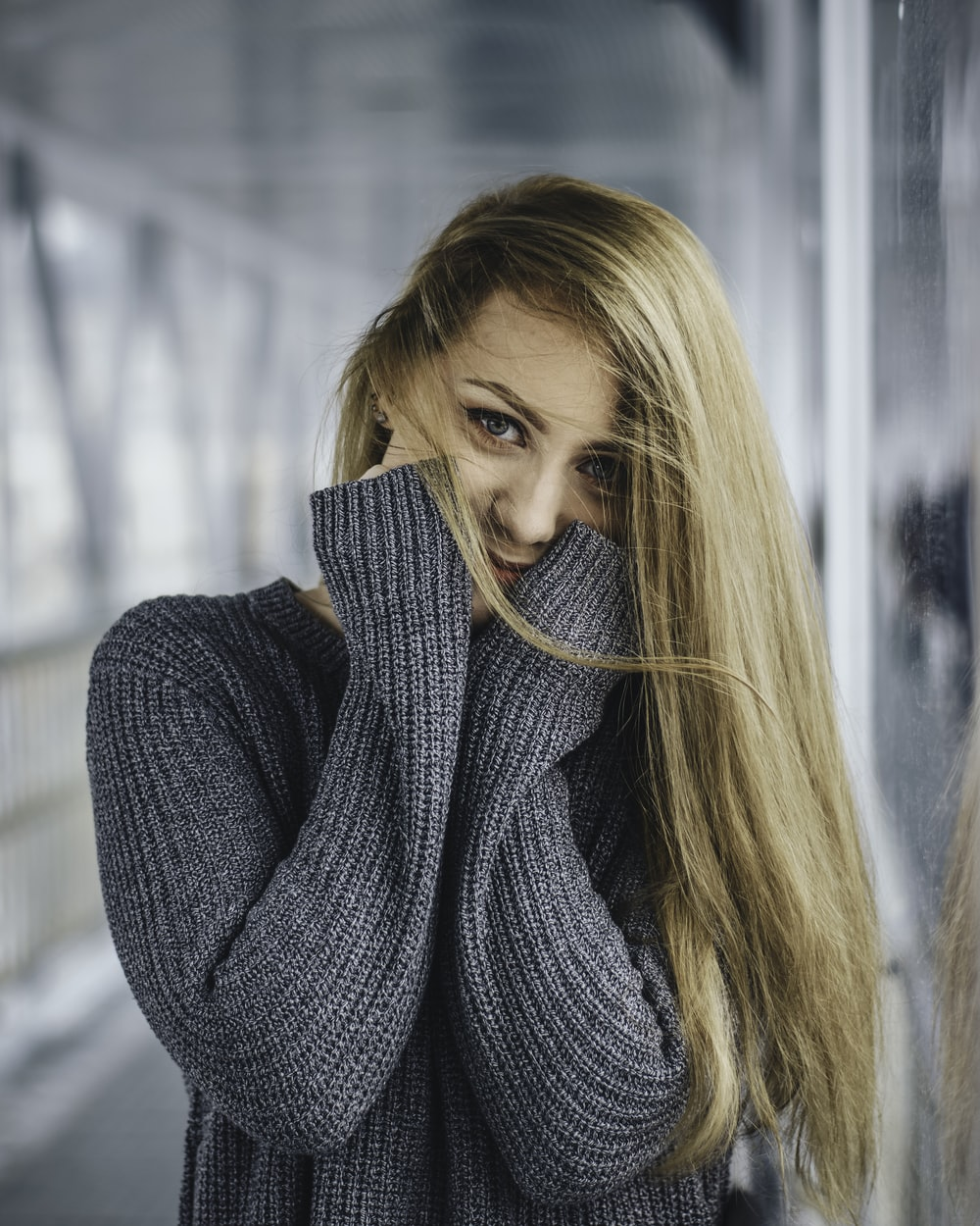 woman in gray knitted sweater with hands on cheeks