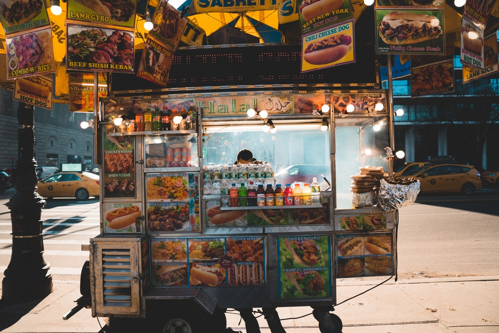 person standing behind food cart during nighttime