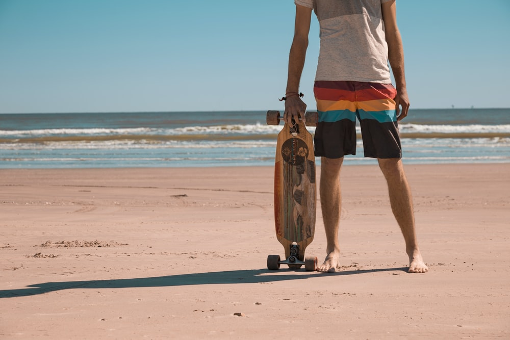 man holding longboard standing at sea shore