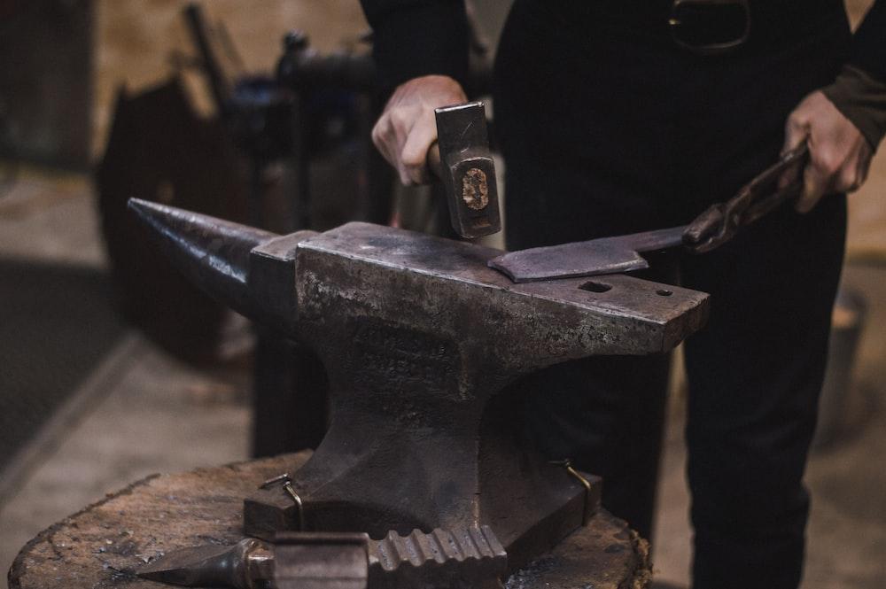 person hammering metal using hammer