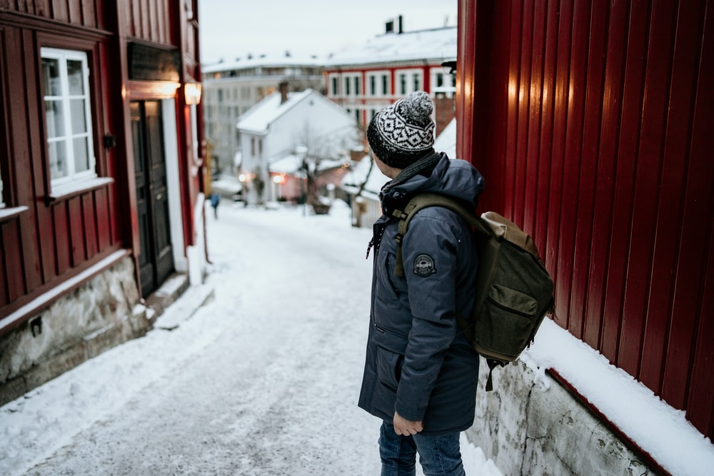 person carrying backpack standing between houses