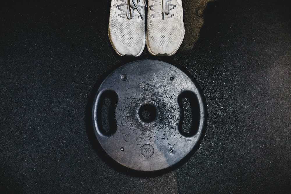 black weight plate beside white sneakers