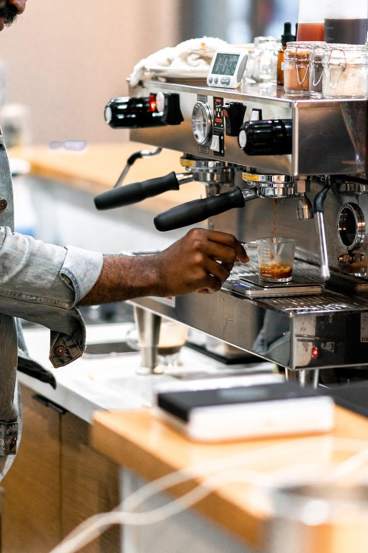 man using grey coffee machine