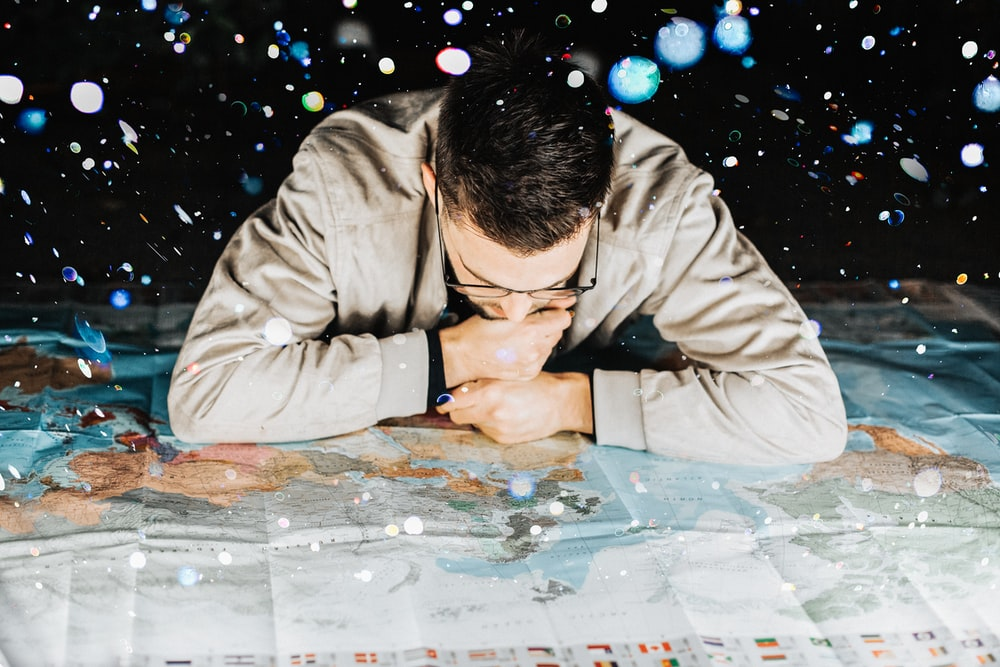 man in grey jacket leaning forward on map