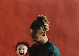 smiling man carrying child and playing