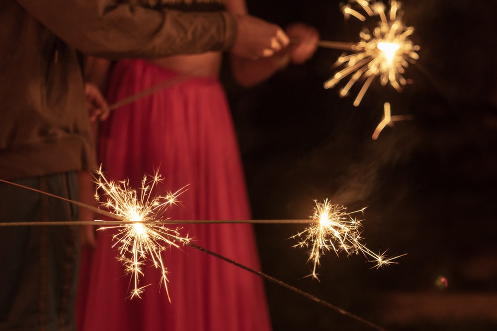 man and woman holding sparklers