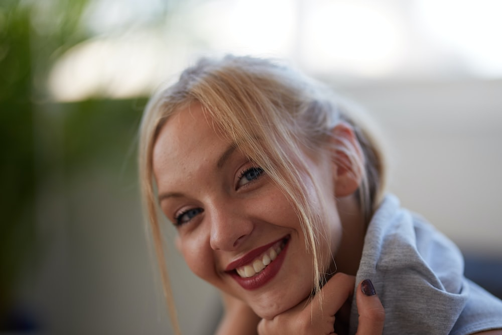 smiling woman in grey hoodie with red lipstick