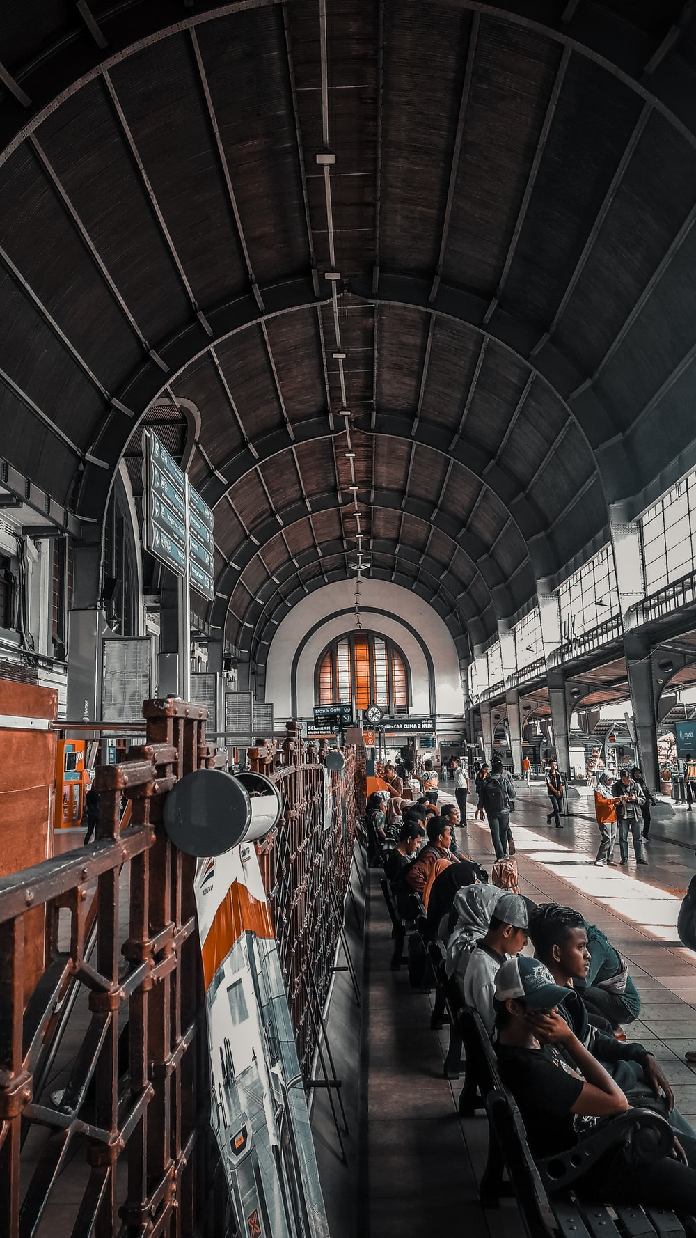 people sitting inside train station during daytime