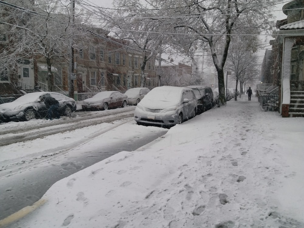 snow covering parked cars on the street