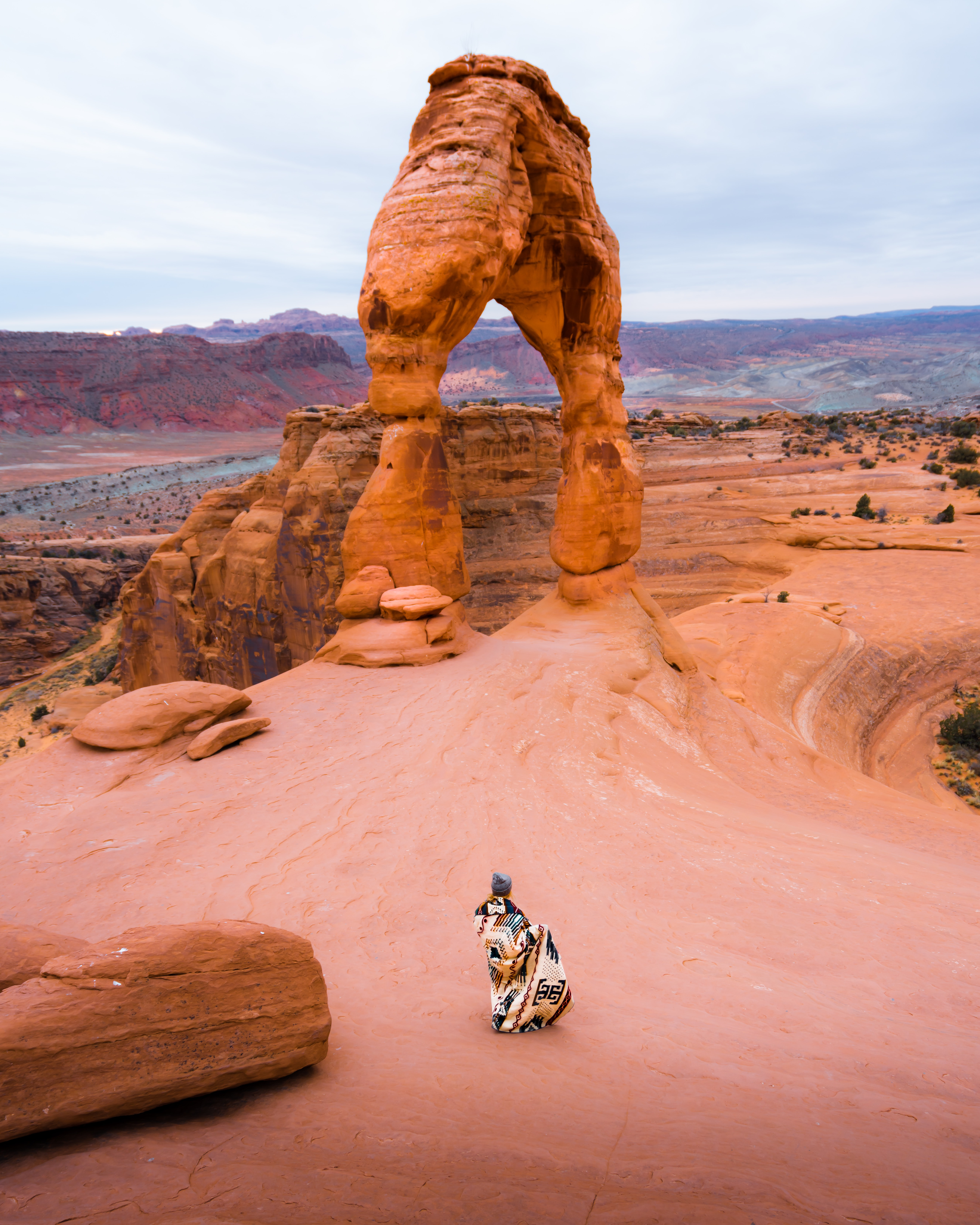 aerial view photography of woman standing near rock formation during daytime