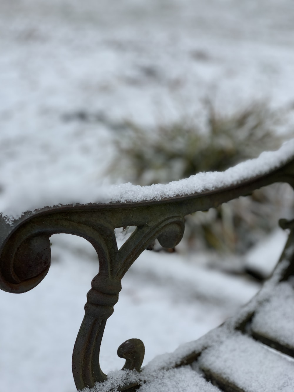 brown metal bench covered by snow