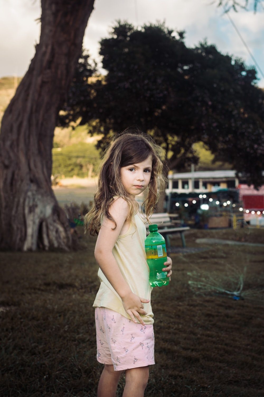 girl standing and holding bottle in brown field