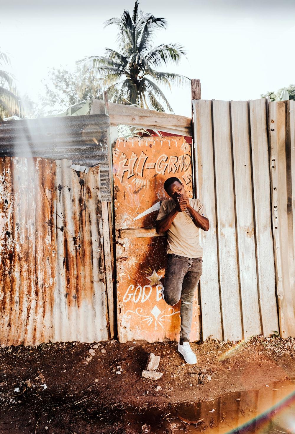 man standing beside gate