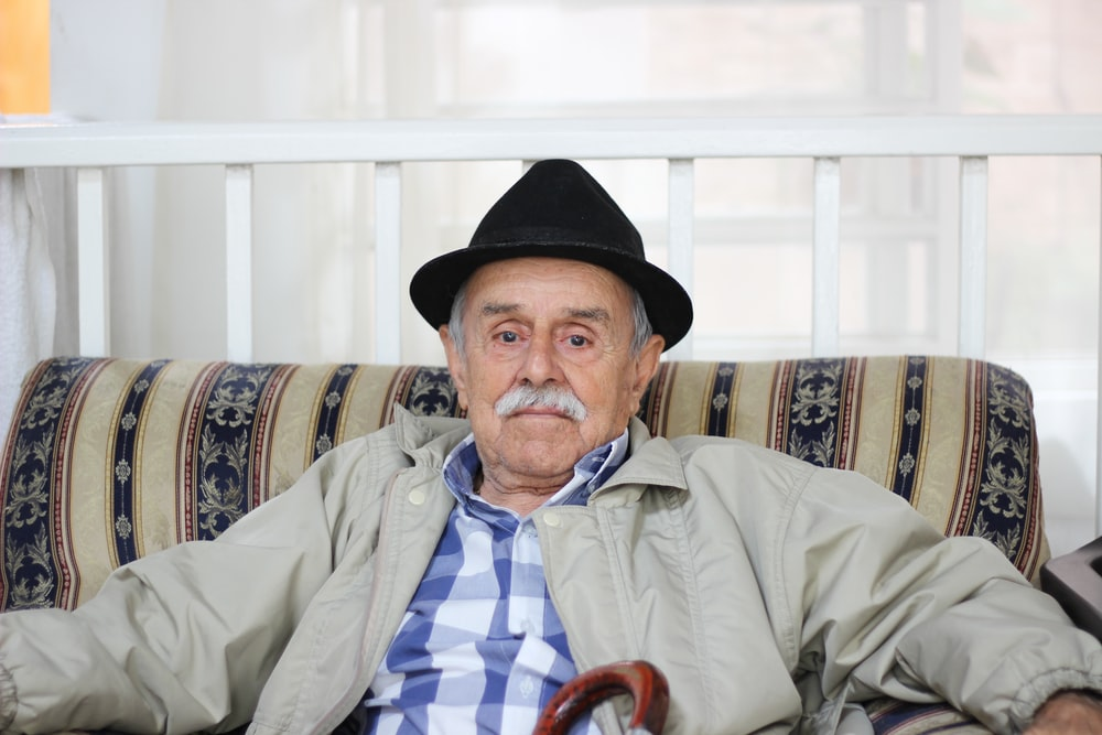 man in grey jacket wearing black hat sitting on couch