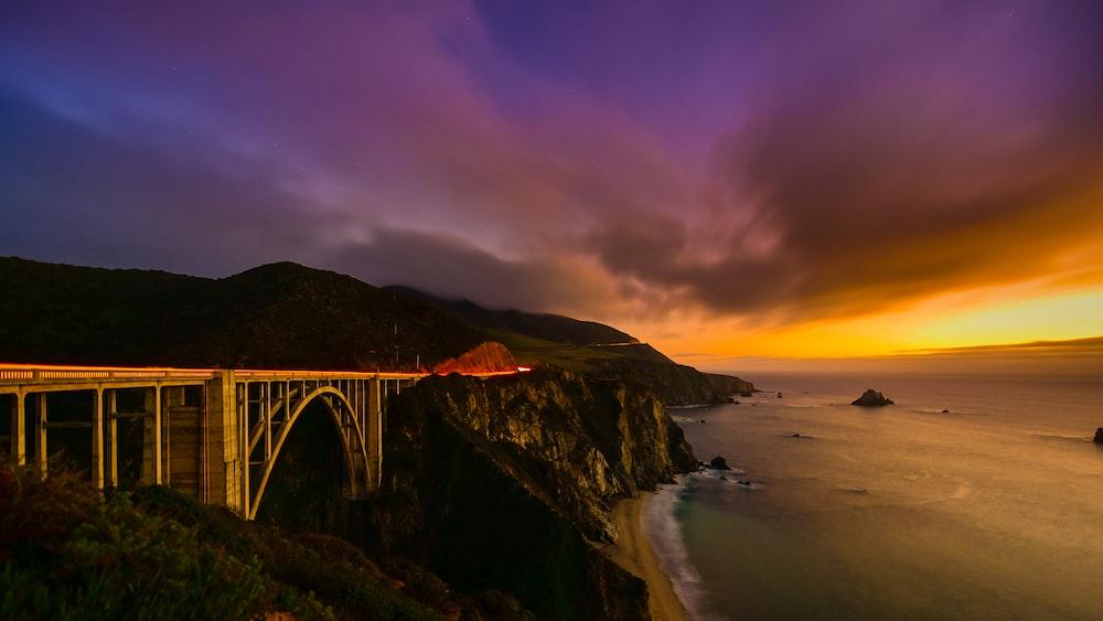 brown suspension bridge beside body of water