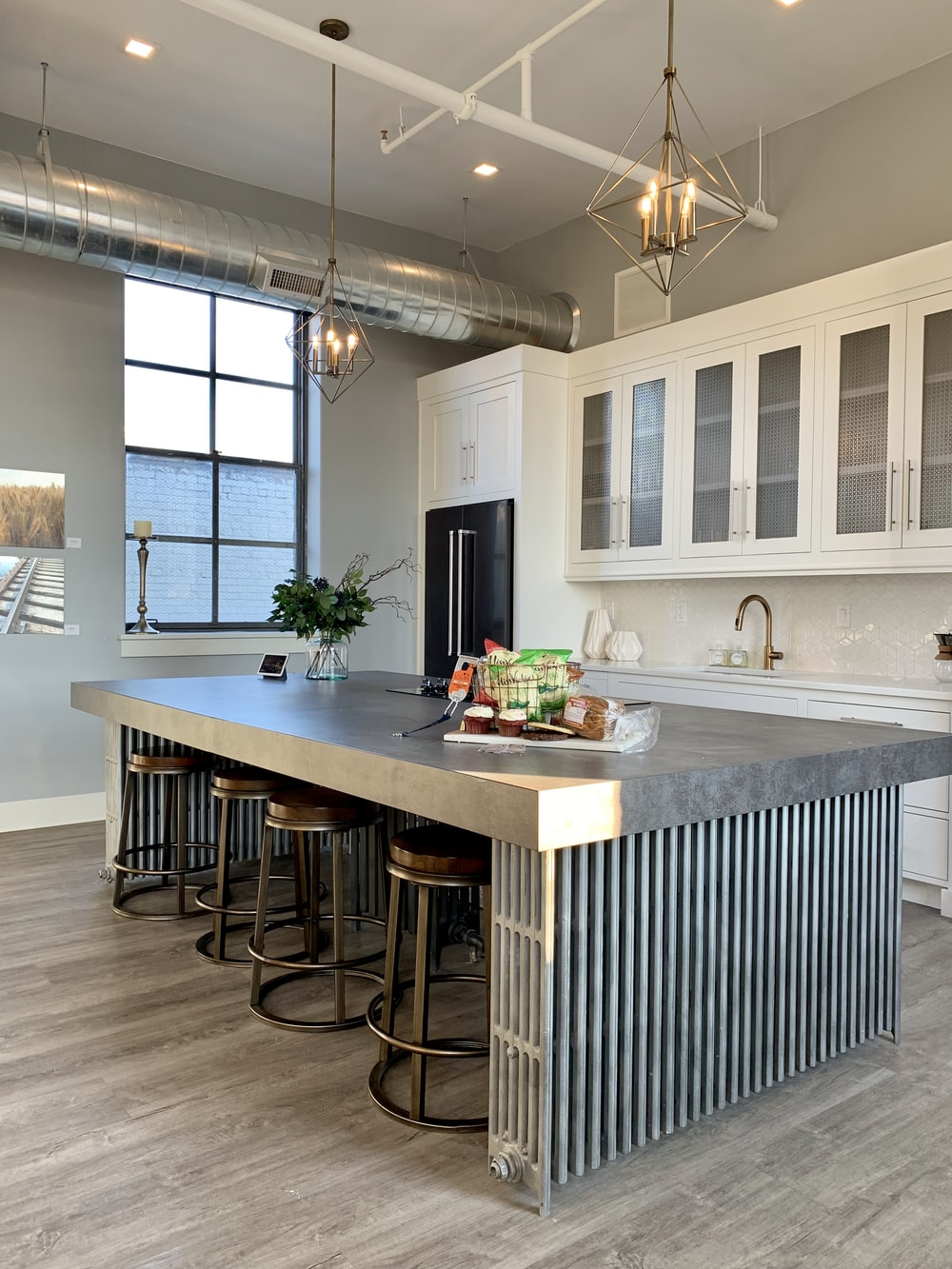 gray metal island table near white wooden kitchen cabinet