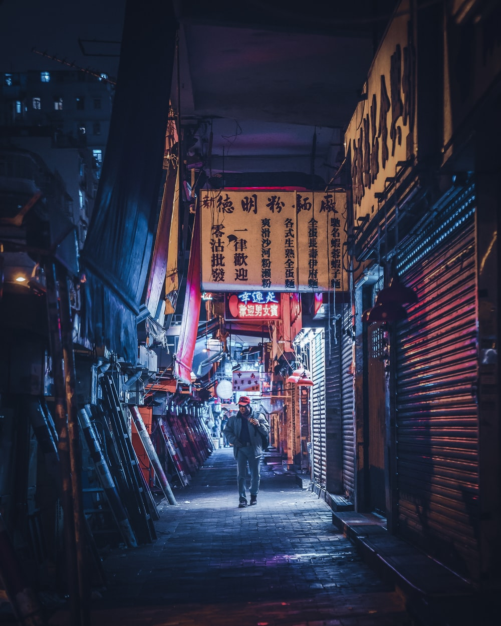 man in denim jacket and jeans walking on pathway near buildings at night