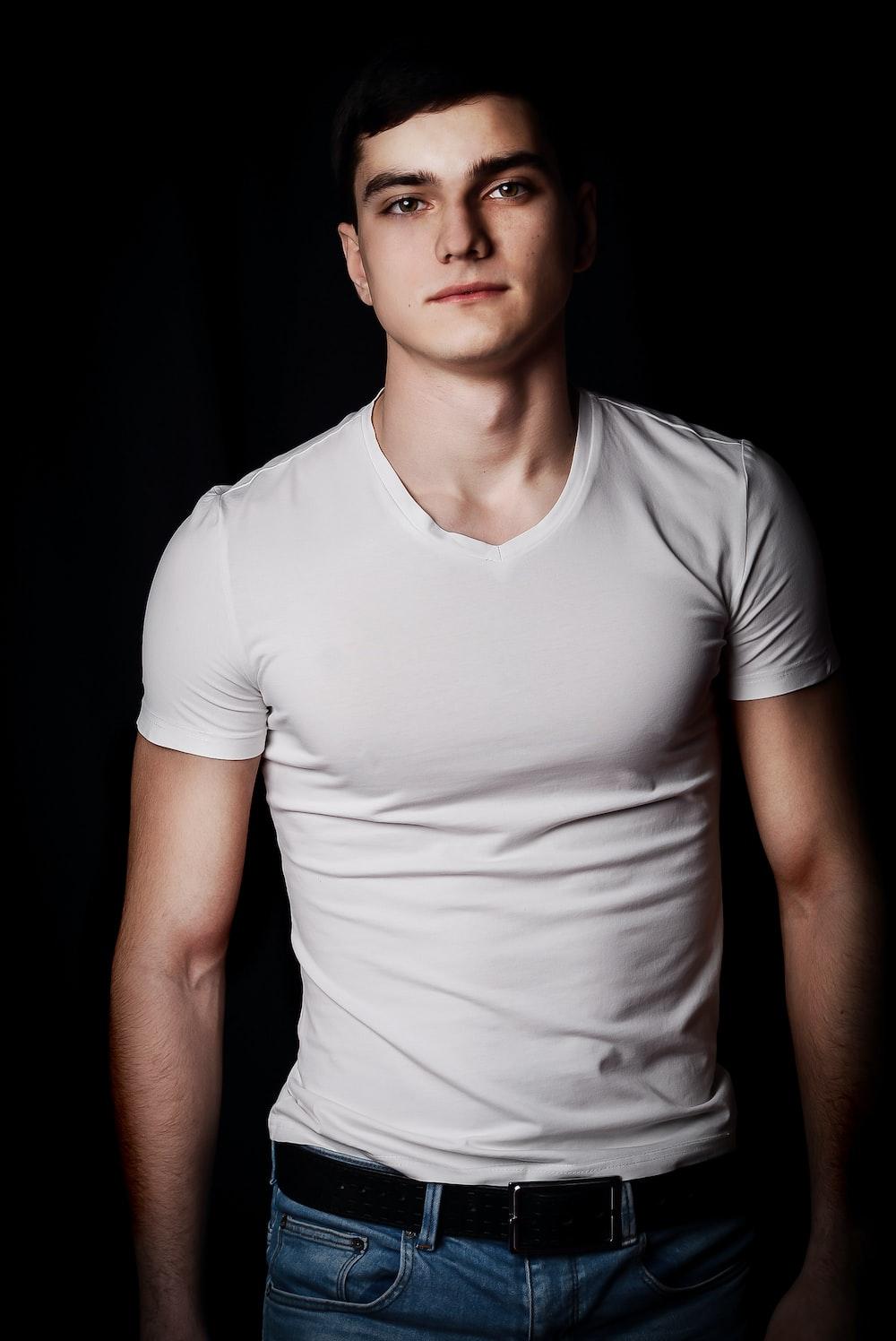 man in white V-neck t-shirt and blue denim bottoms