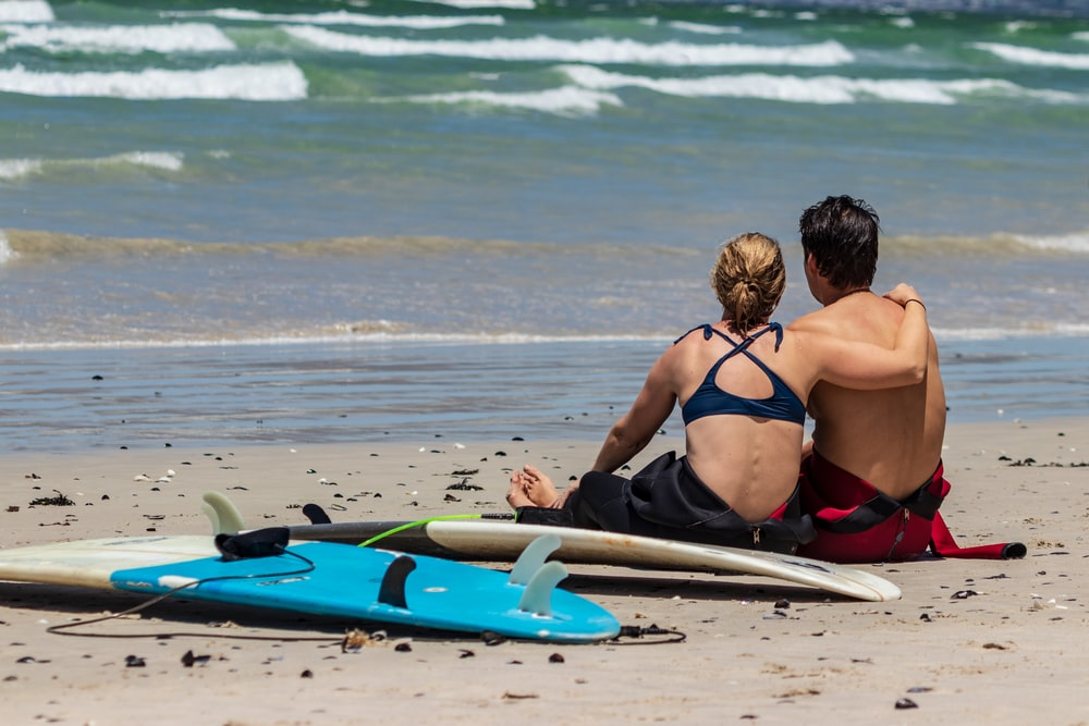 woman and man sitting on shore beside two surfboards during daytime