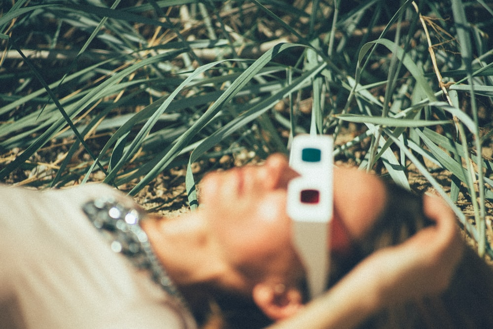 person using 3D glasses lying on grass