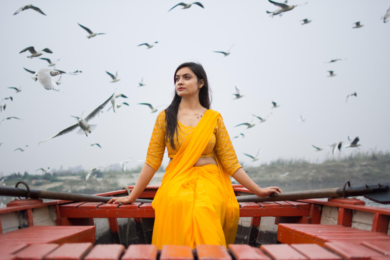woman wearing yellow 2-piece dress sitting on dock