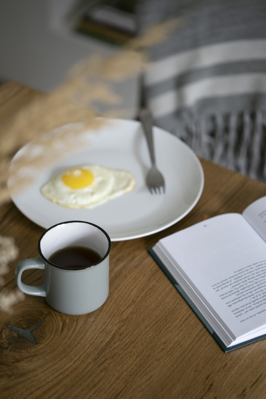 sunny side-up on plate beside a half filled mug
