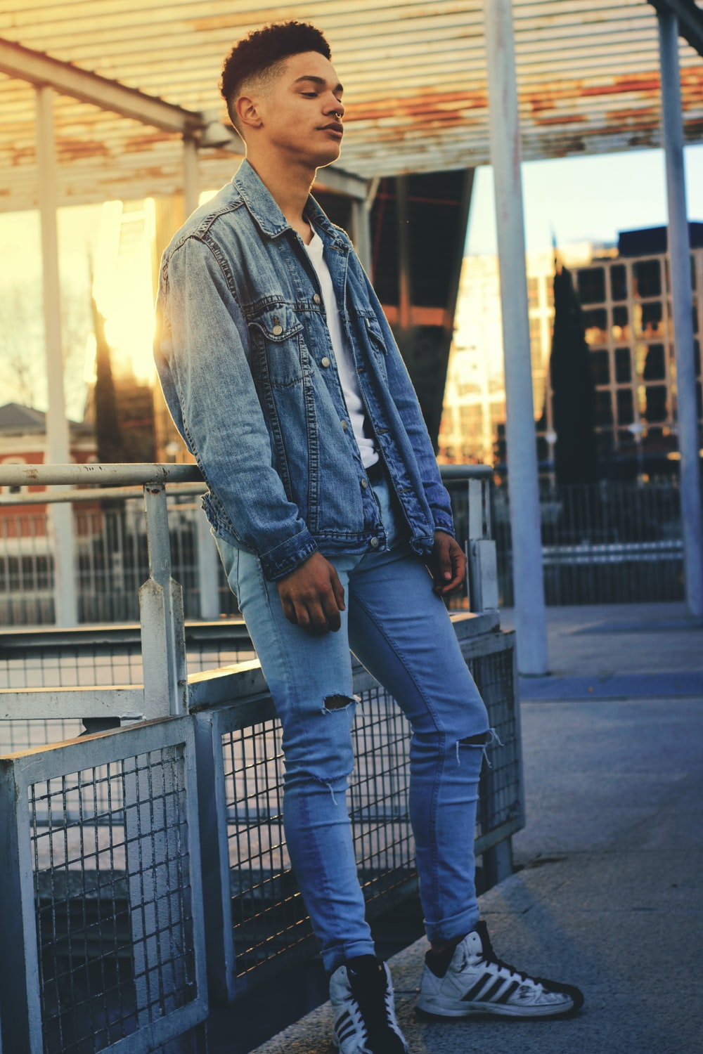 man in blue denim jacket leaning on safety hand rail