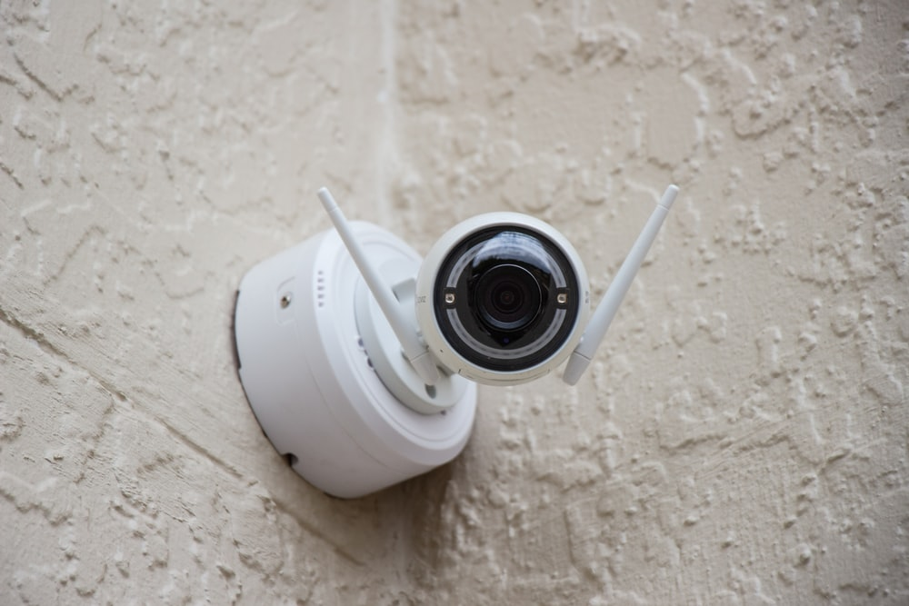 white surveillance camera hanging on wall