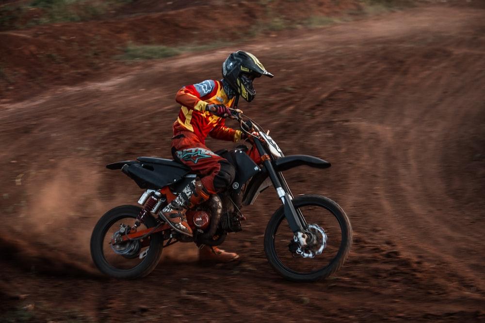 biker on dirt road during daytime