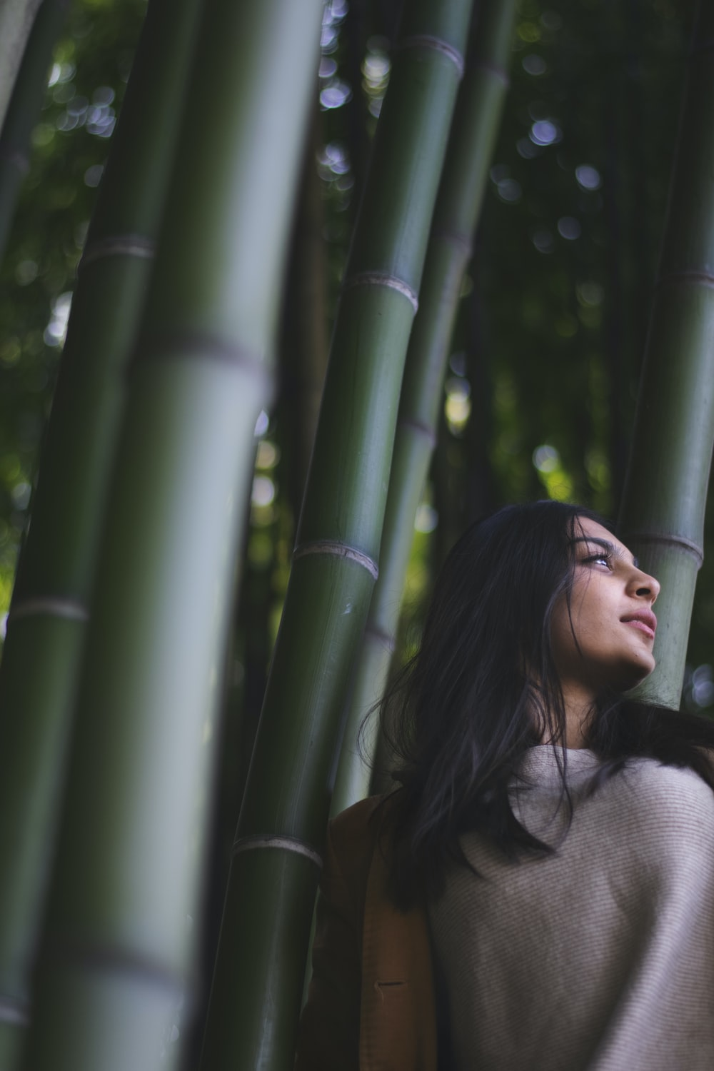 smiling woman leaning on bamboo tree