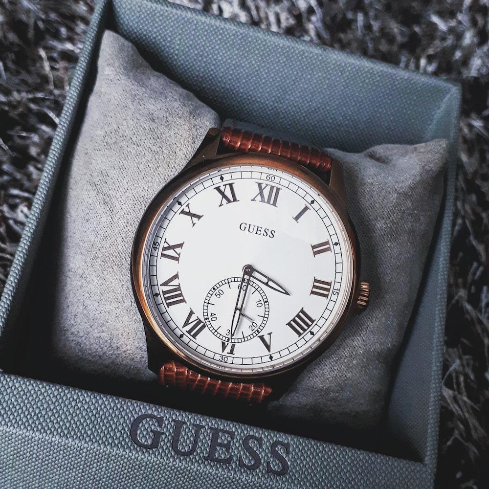 round Guess analog watch displaying 3: 30 time