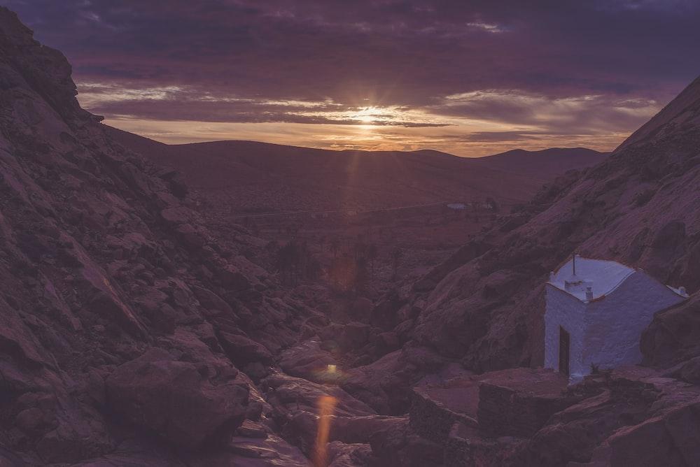 white house on mountain during orange sunset