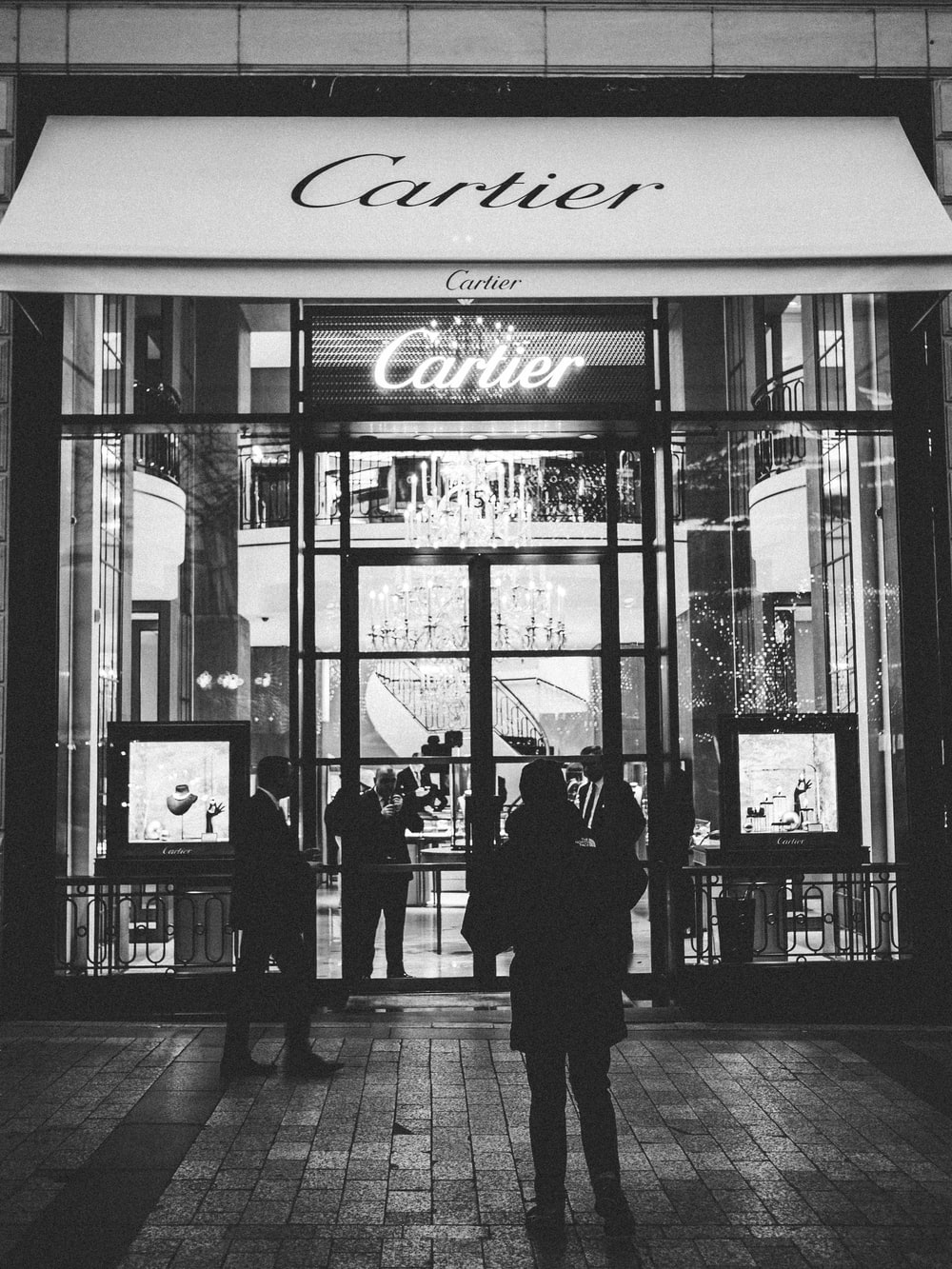 person standing front of Cartier signage