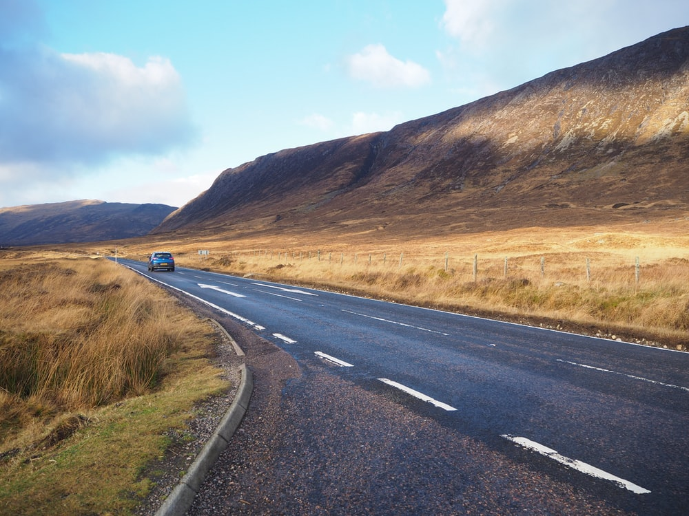 black car travelling on road during daytime