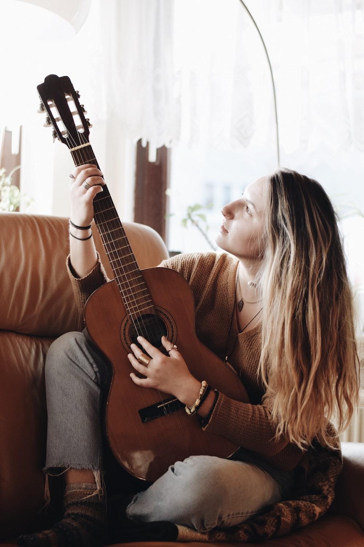 woman playing classical guitar near window inside room