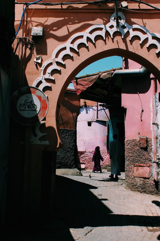 man standing beside pink house