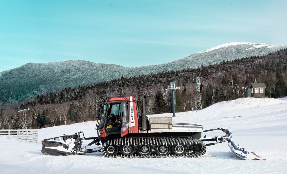 red snow bulldozer on snow-covered mountain during daytime