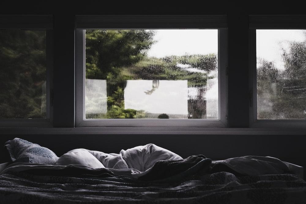 gray comforter beside window