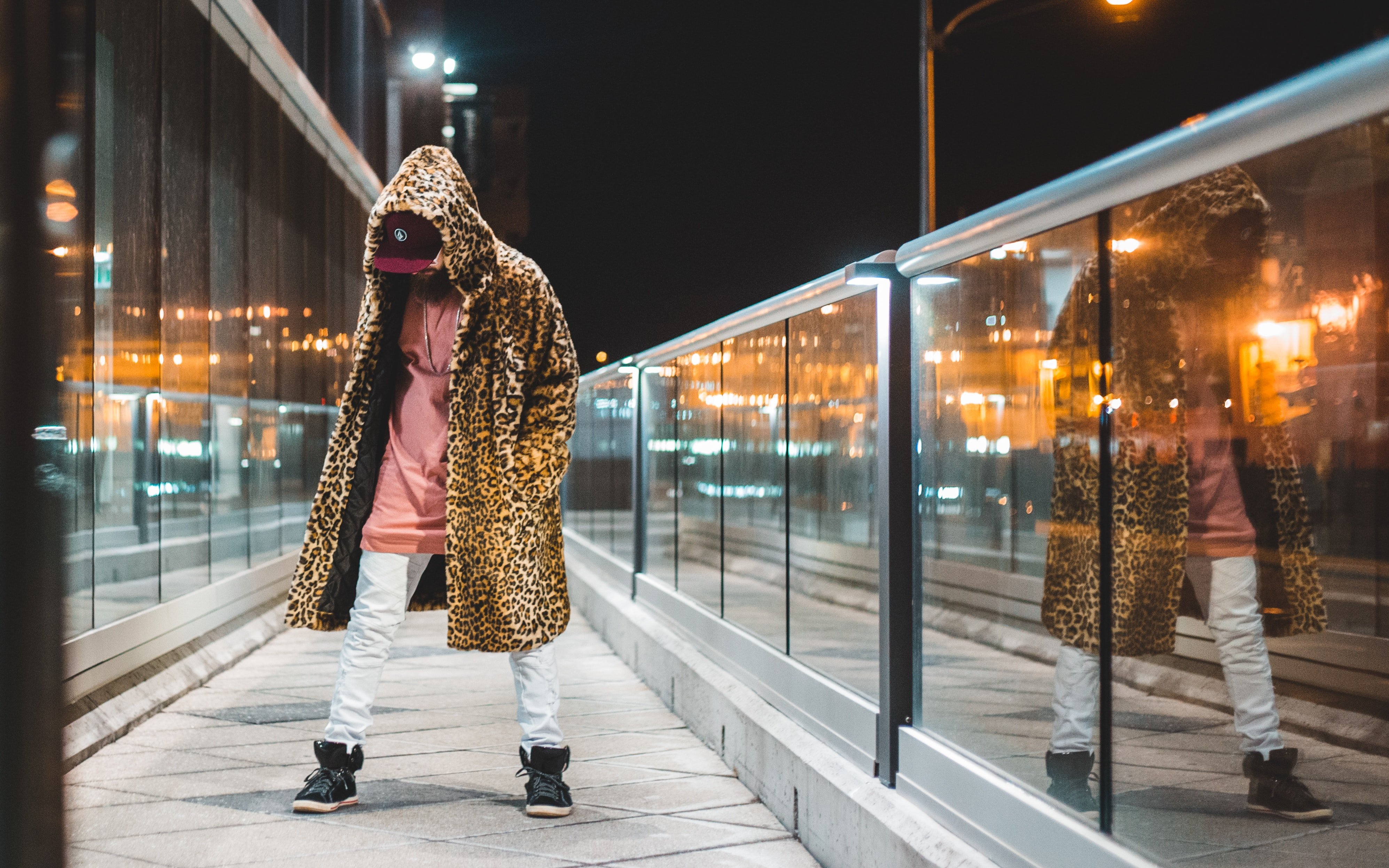 man wearing pink shirt, white pants, black high-top sneakers and brown leopard print hooded coat at night