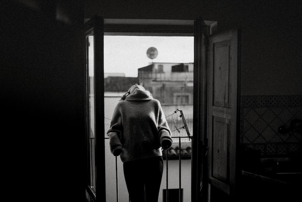 grayscale of woman standing in front of door