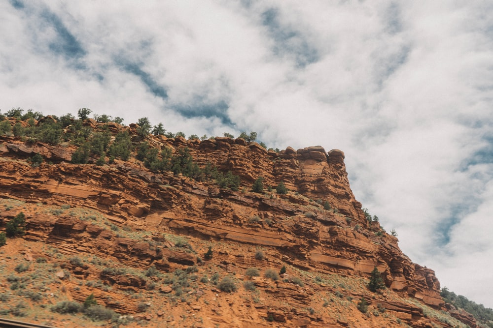 low-angle photography of brown mountain under cloudy sky during daytime