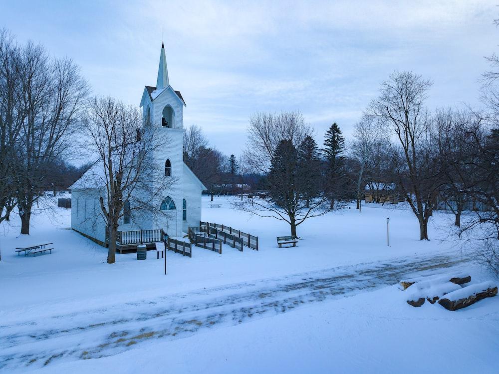 snow covered church under grey cloudy sky