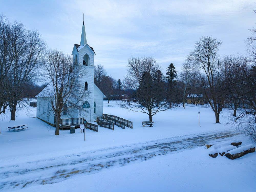snow covered church under grey cloudy sky